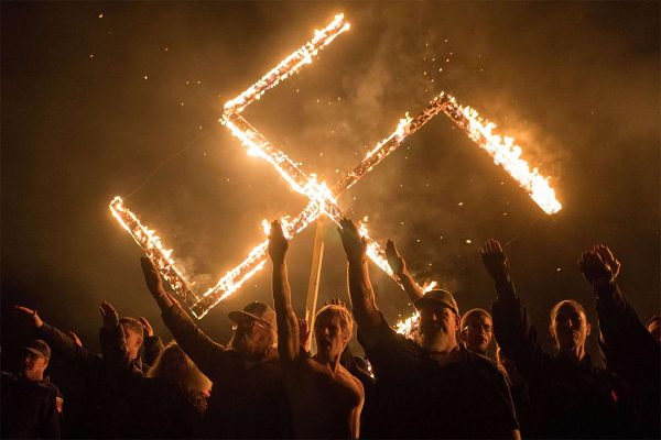 Members of the National Socialist Movement, one of the largest neo-Nazi groups in the US, hold a swastika burning on April 21, 2018, in Draketown, Georgia.