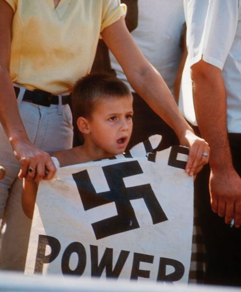 """A young boy holds up a """"White Power"""" sign at a counter-demonstration of a civil rights march, in 1966."""