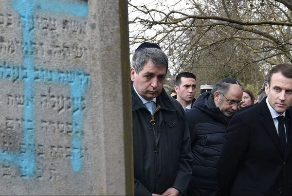 French President Emmanuel Macron looking at a grave vandalized with a swastika during a visit to the Jewish cemetery in Quatzenheim, France.