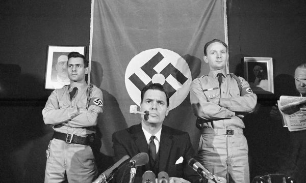 American Nazi Party founder George Lincoln Rockwell with paintings of Hitler and George Washington.